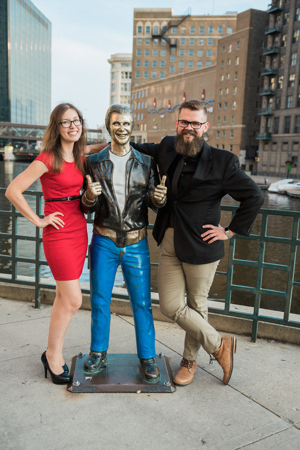 Engaged couple puts their arm around The Bronze Fonz on the Milwaukee Riverwalk.