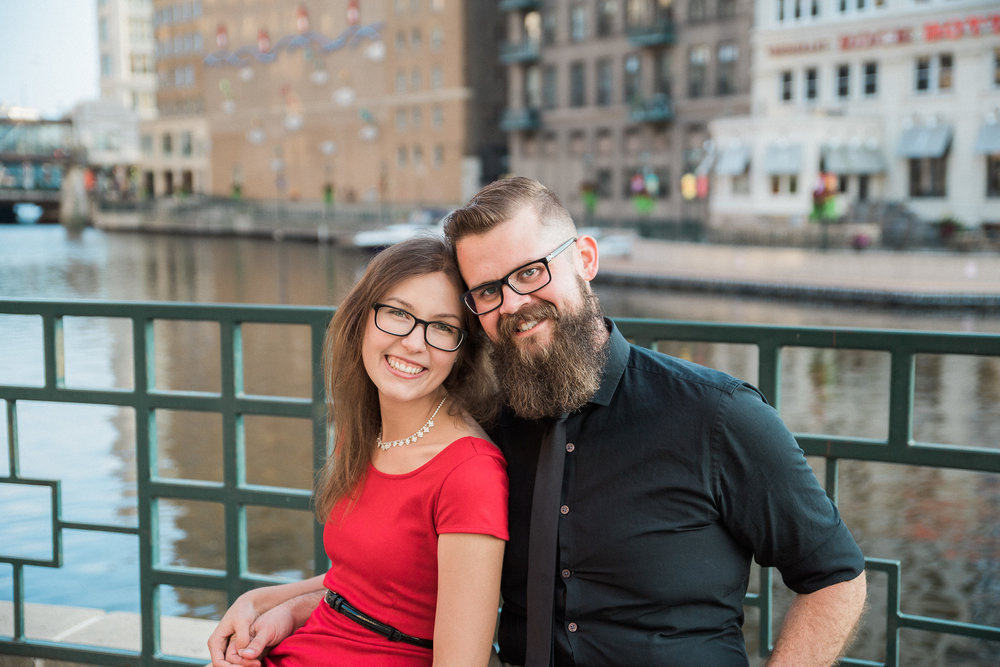 Engaged couple sits together on the Milwaukee Riverwalk.