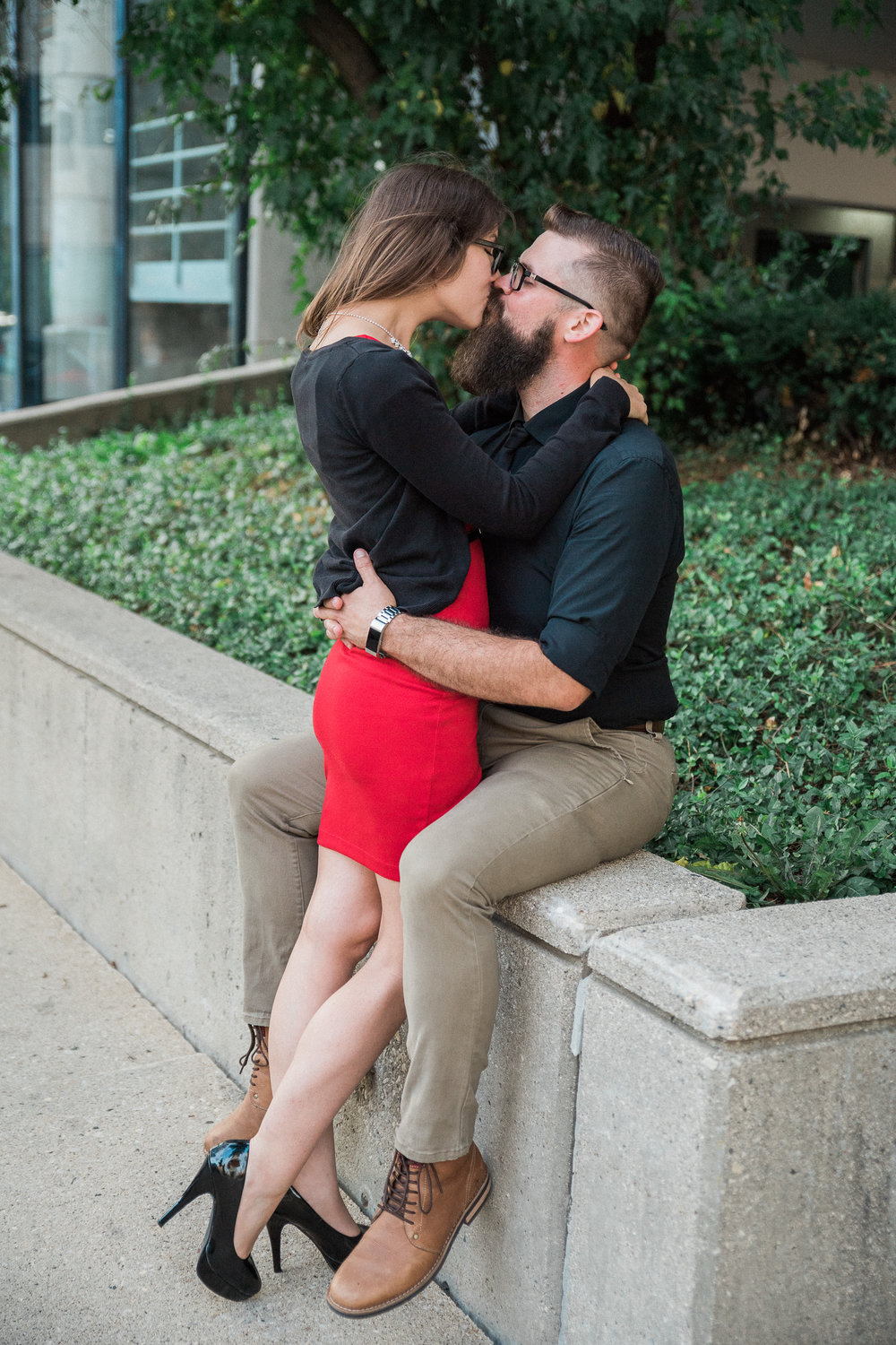 Man sits on a concrete ledge as his fiance stands in between his legs and kisses him.