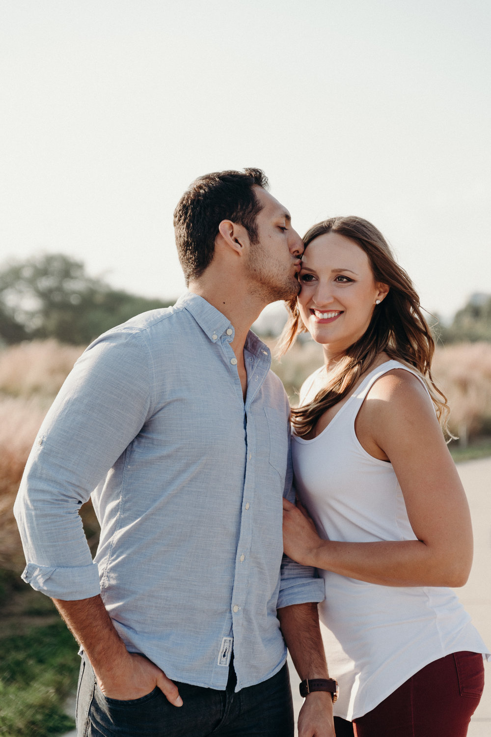 Woman smiles as her fiancé kisses her on the forehead.