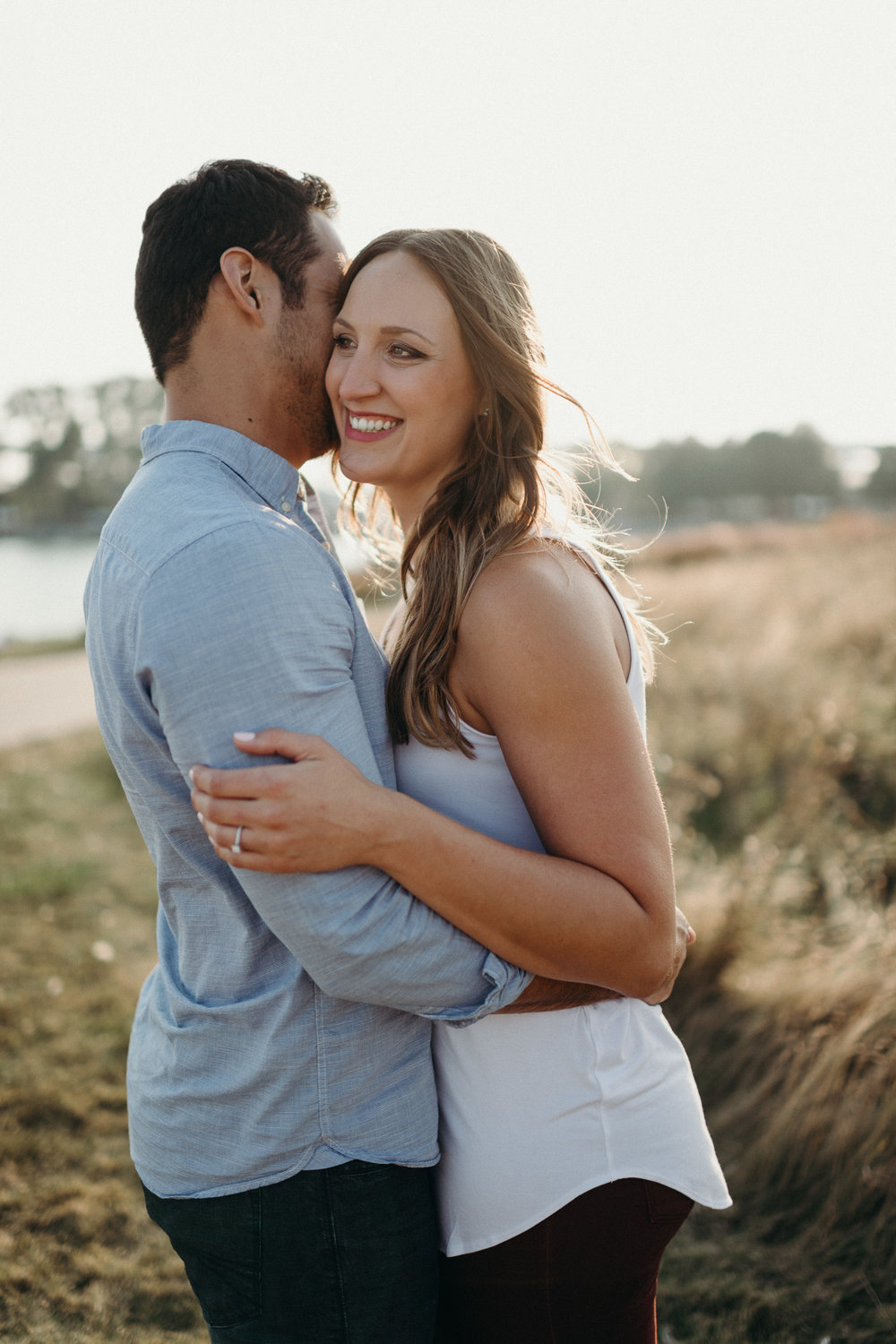 Woman laughs as her fiancé whispers in her ear.