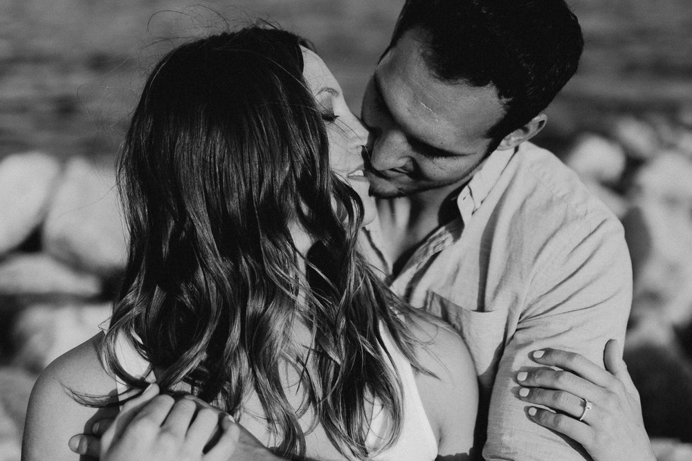 Man wraps his arms around his fiancé and leans in to kiss her.