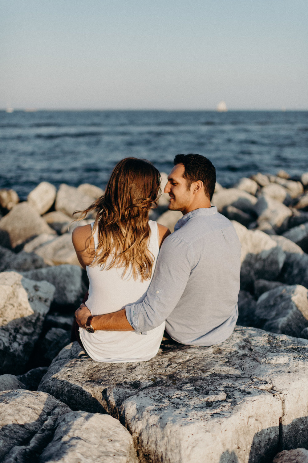 Engaged couple looks at each other while sitting on a rock overlooking Lake Michigan.