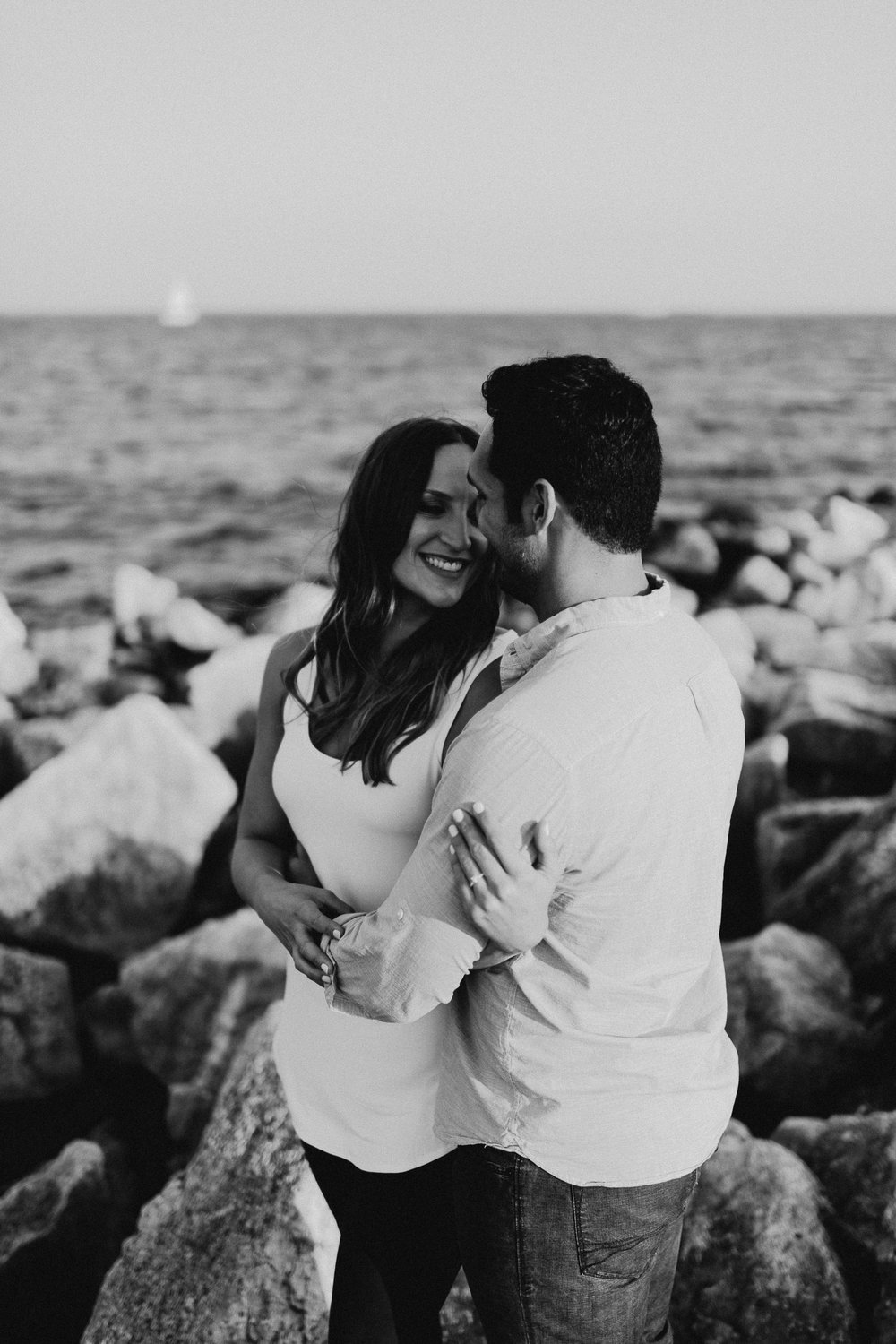 Engaged couple holds each other and smiles as they stand on rocks overlooking Lake Michigan.