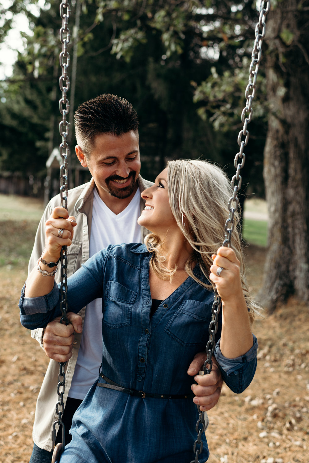 Man pushes his fiancé on a swing as they smile at each other.