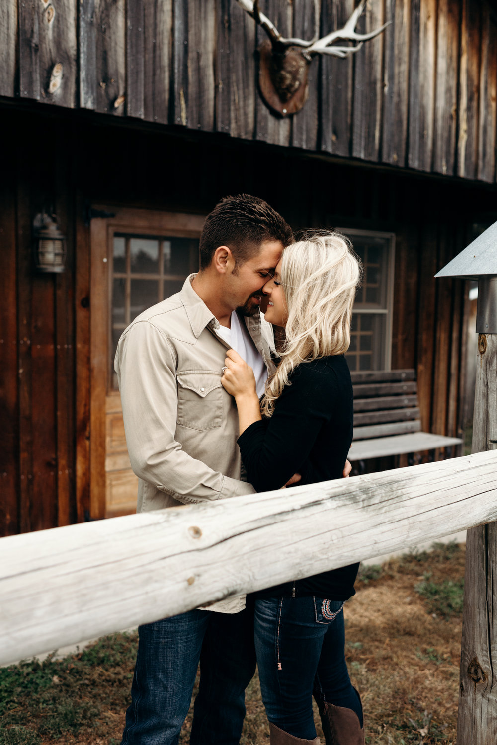Engaged couple smiles at each other in front of a wooden cabin.