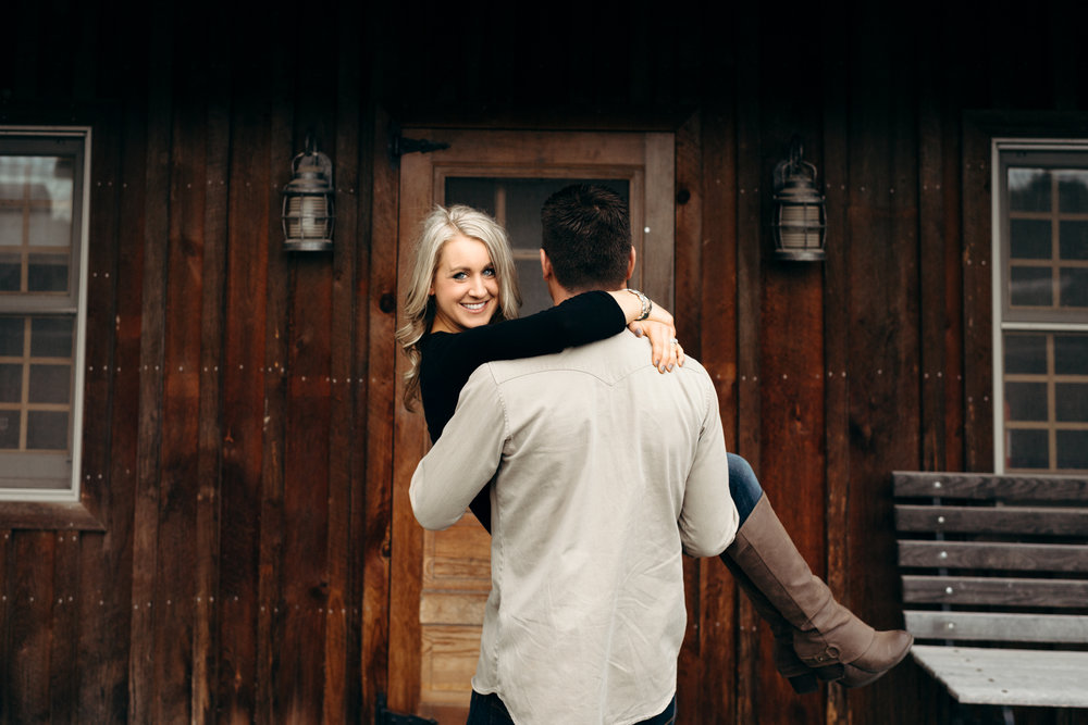 Man carries his fiancé toward the door of a wooden cabin.