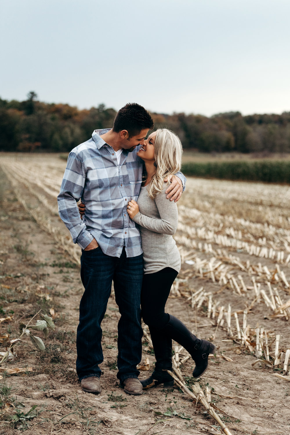 Engaged couple looks into each other's eyes in a harvested cornfield.