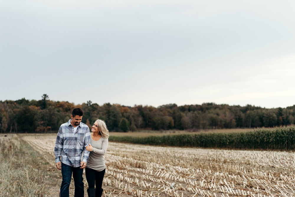 Engaged couple holds hands while walking through a harvested corn field.