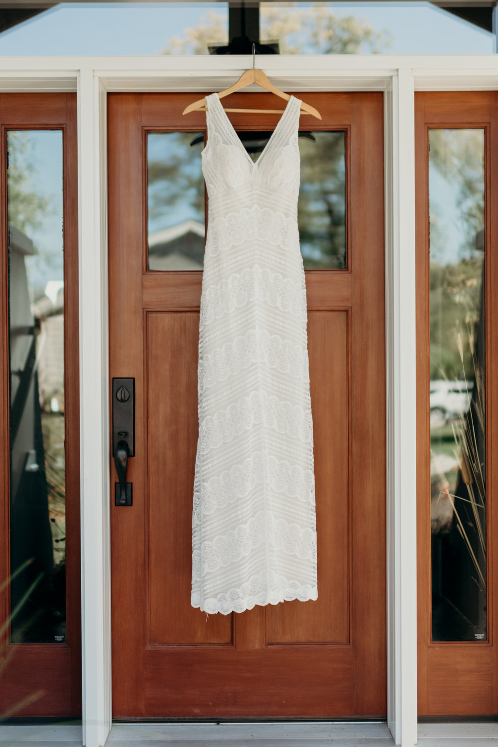 Wedding dress hanging from a door.