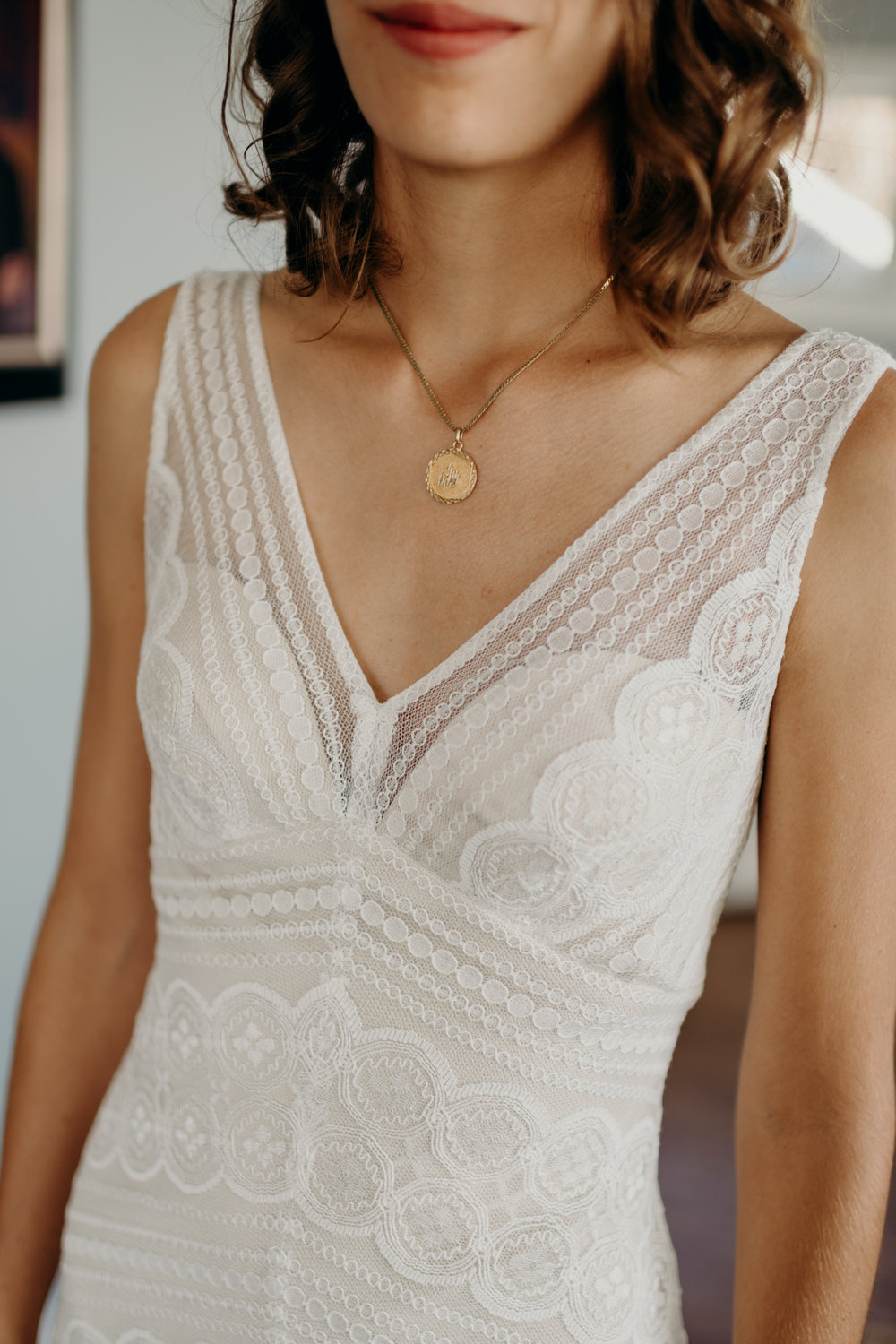 Bride wearing a gold round pendant necklace.