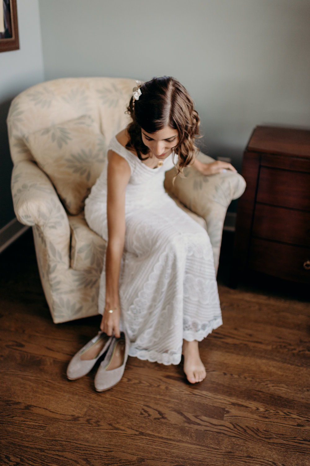 Bride sits on a chair and reaches down for her wedding shoes.