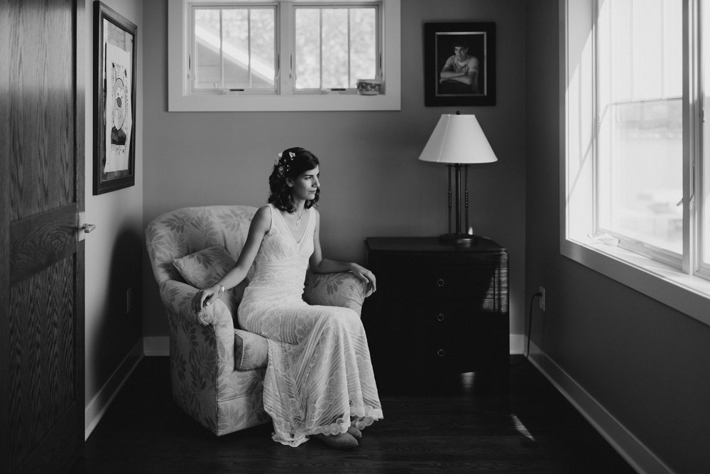 Bride sits on a chair and gazes reflectively out the window.
