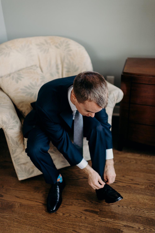 Groom ties his shoes.