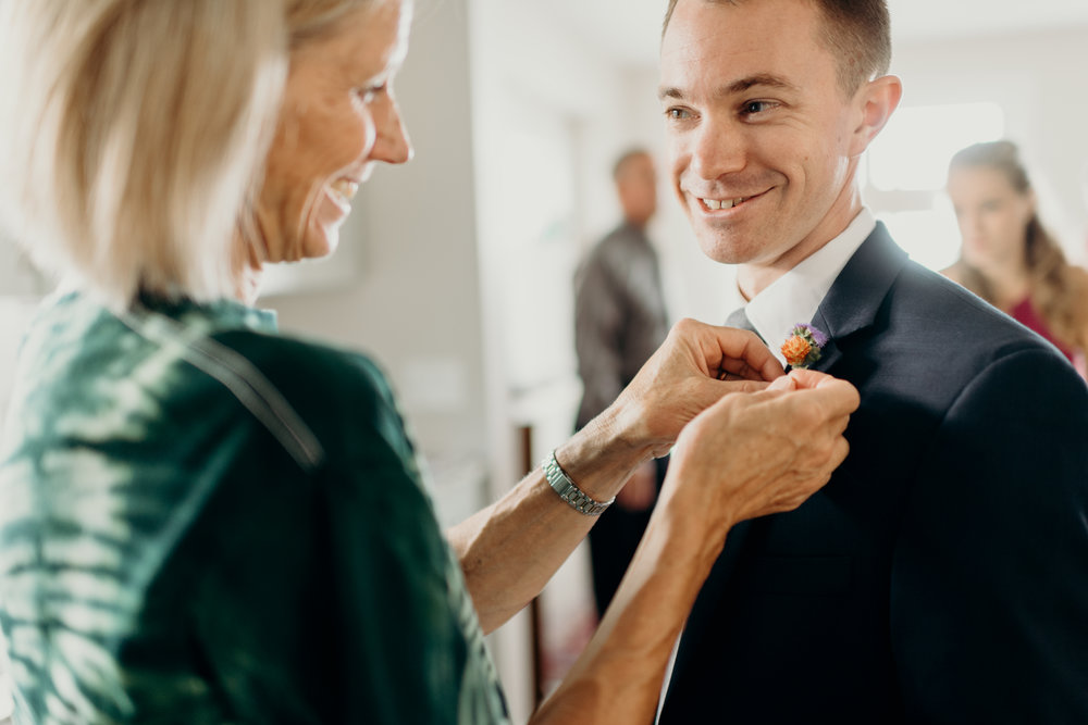 Groom smiles as his boutonniere is pinned on.