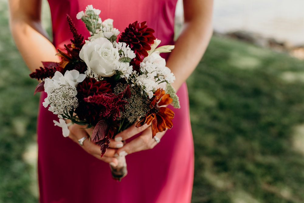 Bridesmaid's white and orange and burgundy bouquet.