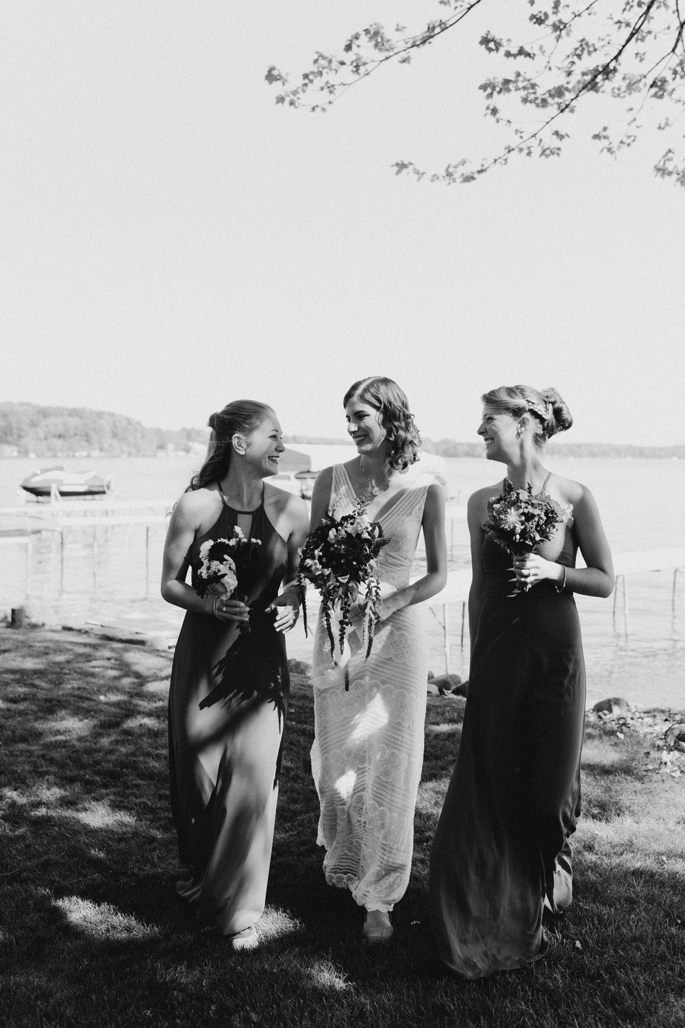 Black and white photo of bride and her bridesmaids smiling at each other.