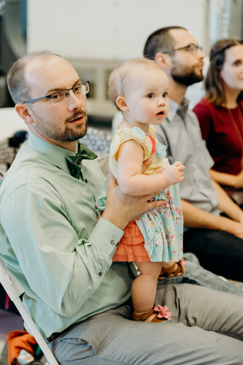 Wedding guests holds his daughter during the ceremony.