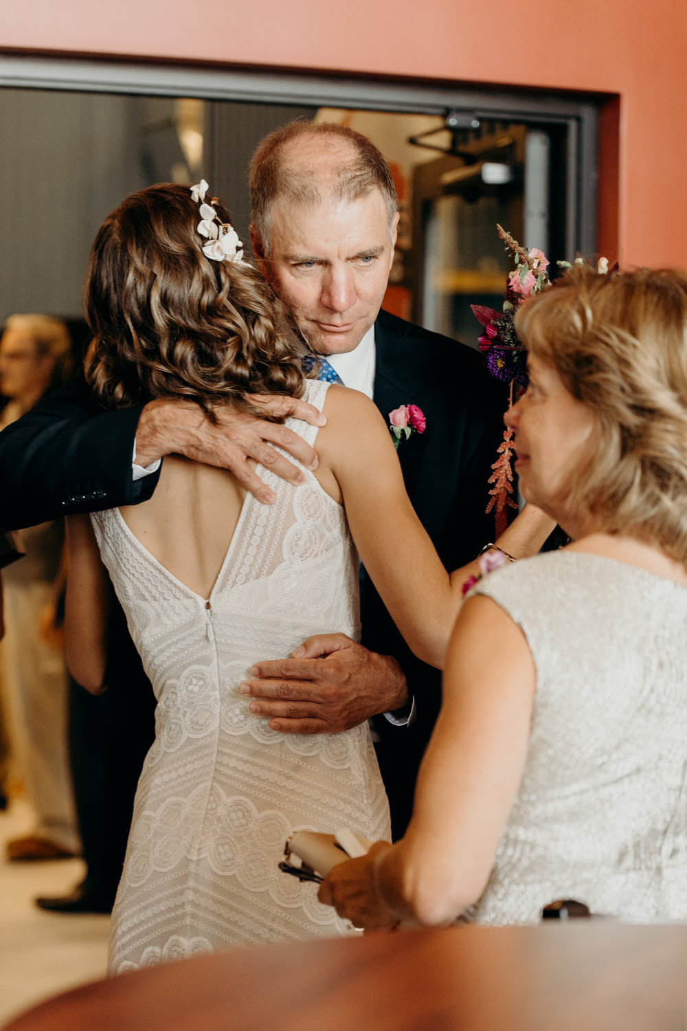 Father of bride hugs her after wedding.