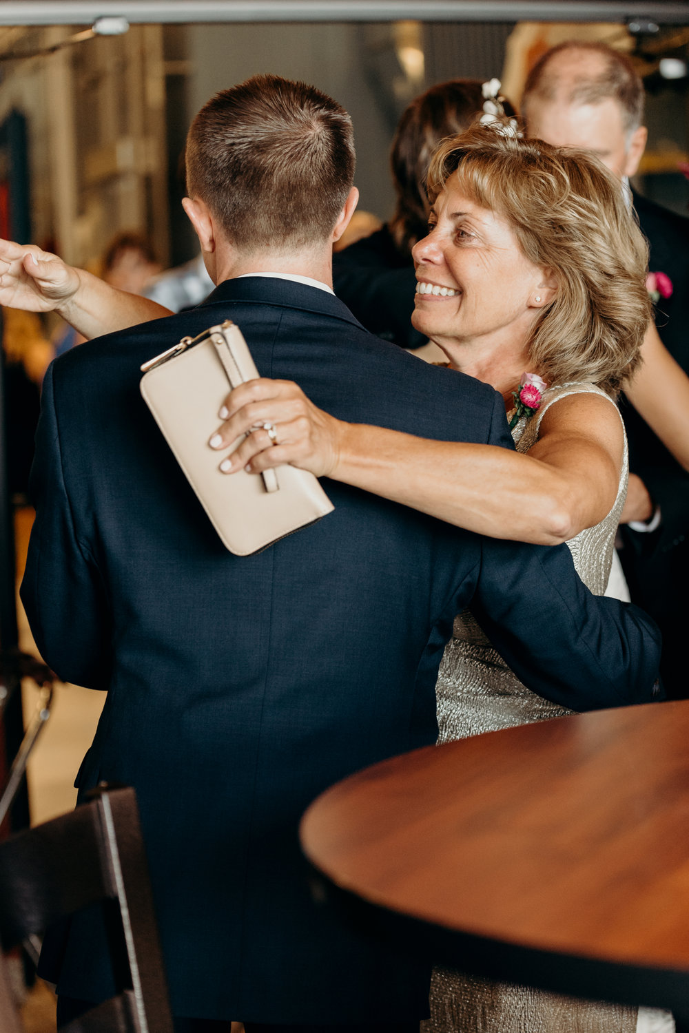 Mother of groom hugs him after wedding.