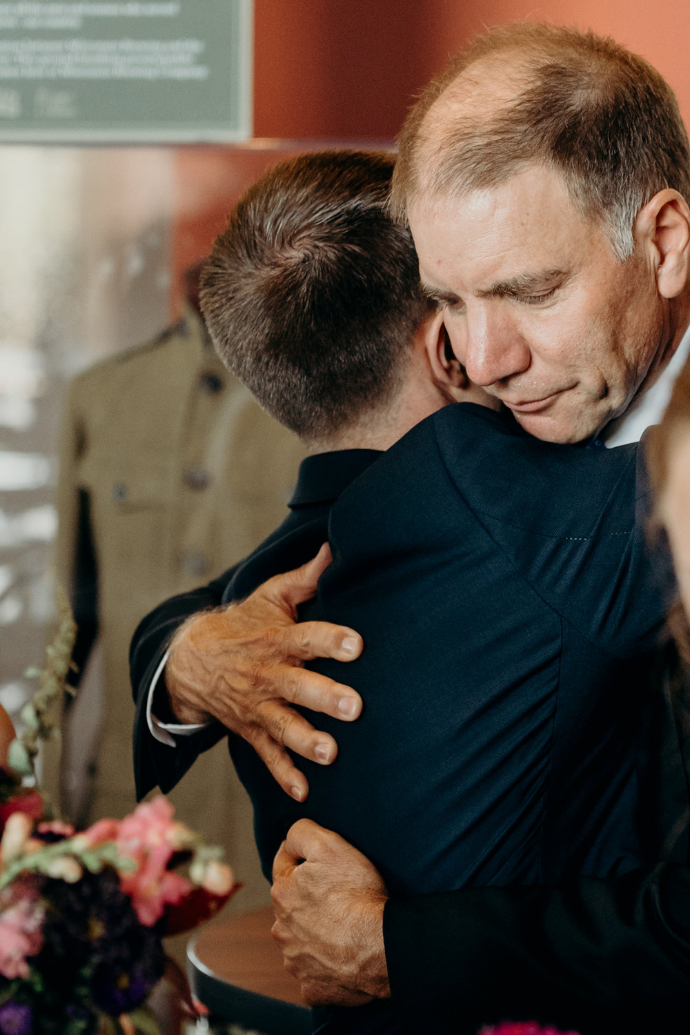 Father of bride hugs his new son-in-law.