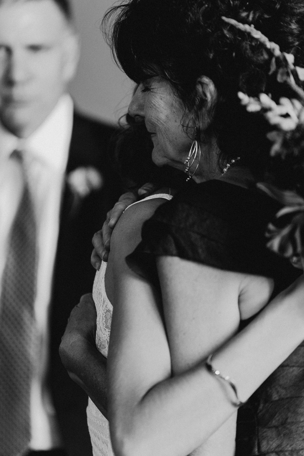 Black and white of mother of bride hugging her daughter.