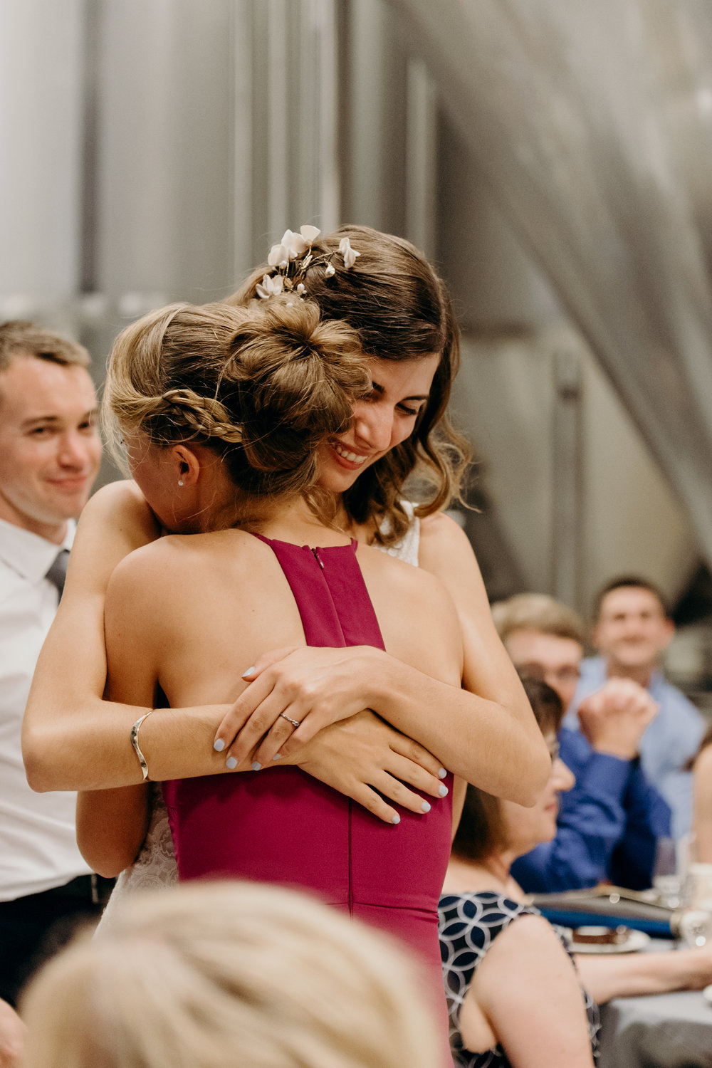 Bride hugs maid of honor after speech.