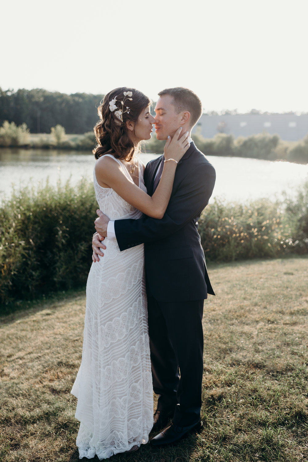 Bride and groom lean in to kiss each other outside by a pond.