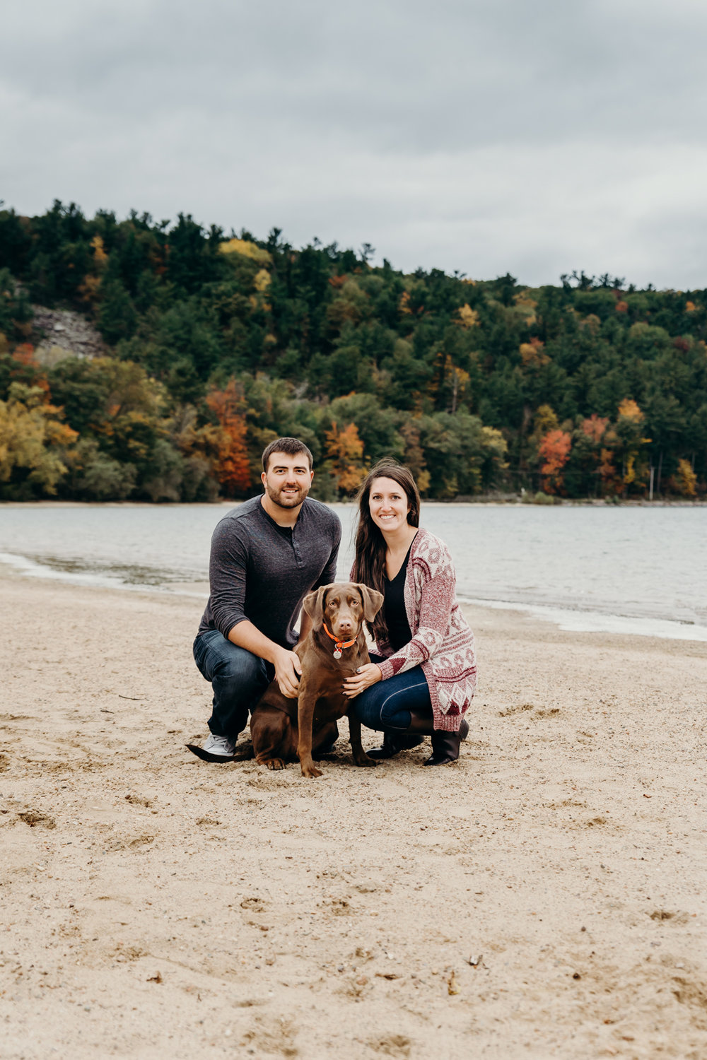Engaged couple poses with their dog on the beach at Devil's Lake State Park in Baraboo, WI.