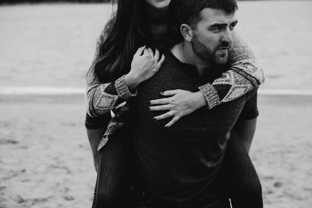 Man looks serious as he carries his fiancé across the beach.