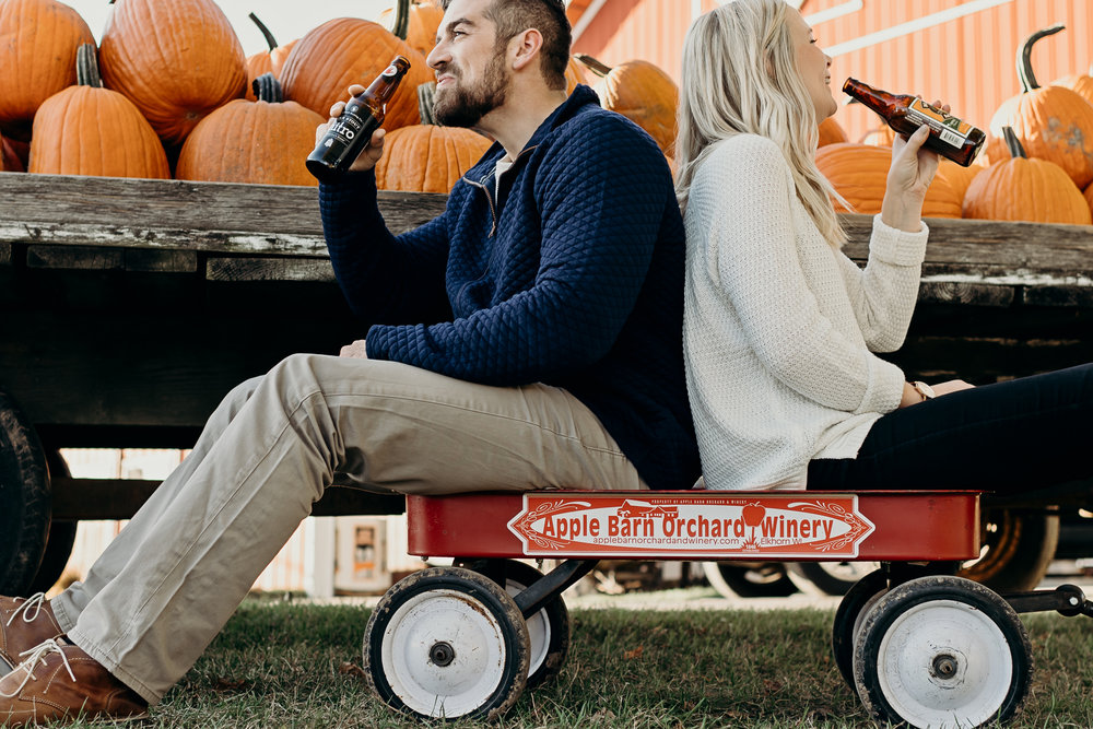 Engaged couple shares a beer while sitting in a red wagon at Apple Barn Orchard and Winery in Elkhart, WI.