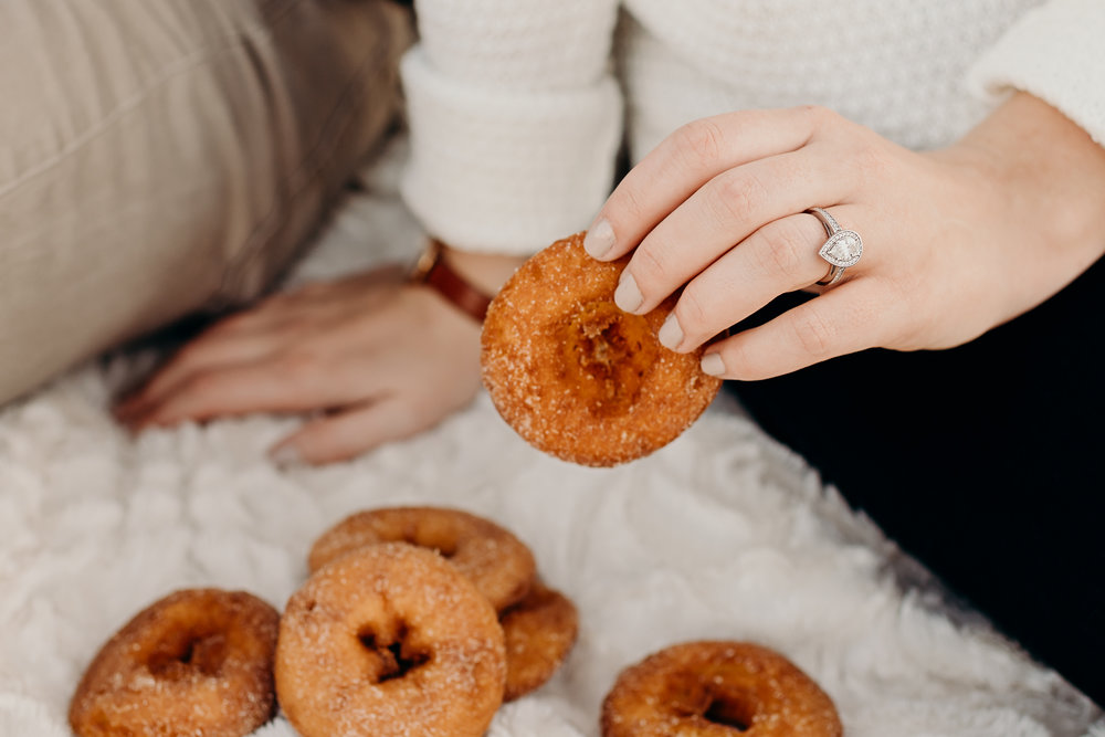 Woman picks up a donut showing off her pear shaped engagement ring.