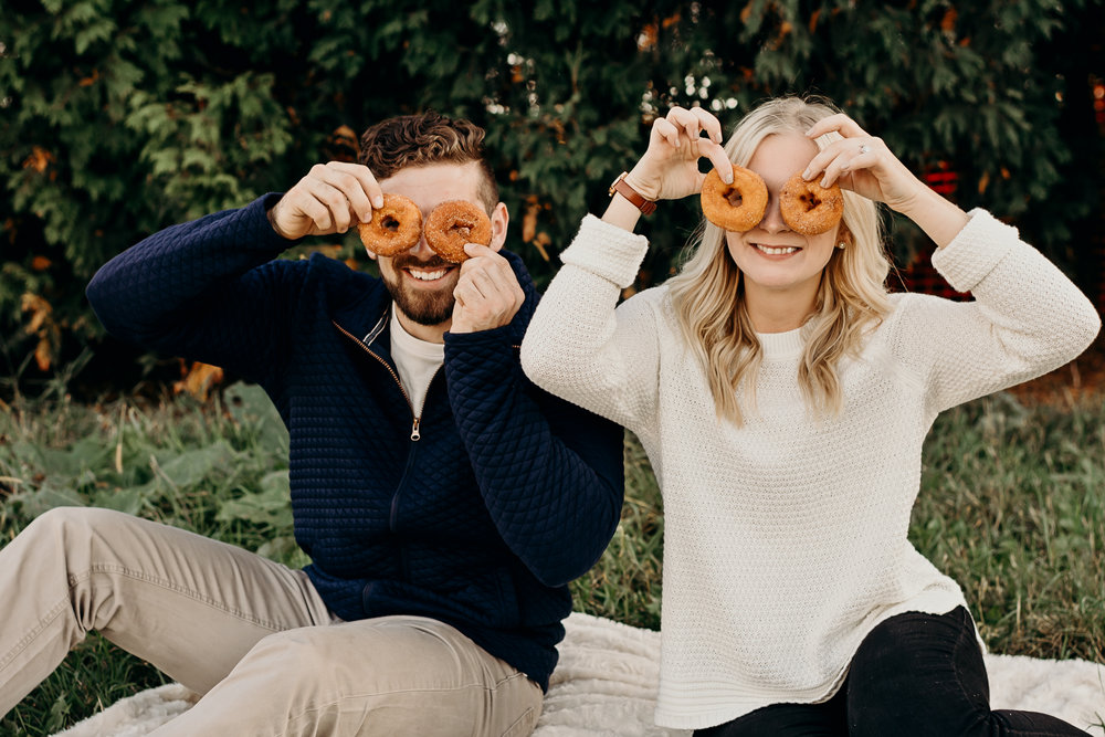 Engaged couple playfully holds donuts over their eyes.
