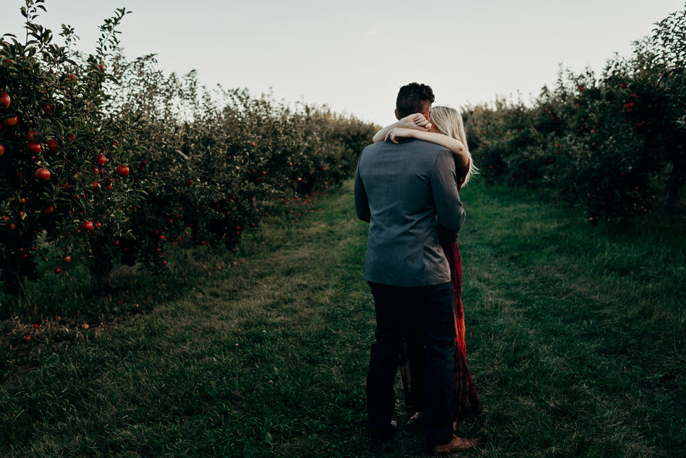 Engaged couple slow dances in an apple orchard.
