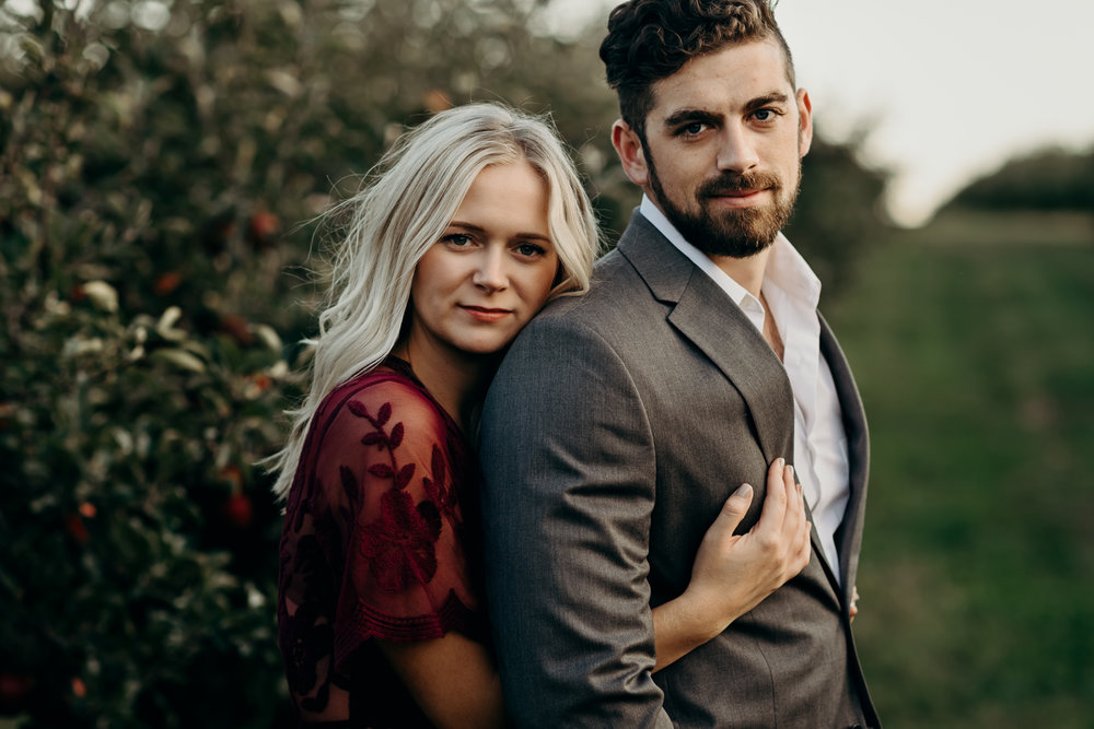 Engaged couple looks serious while standing in an apple orchard.