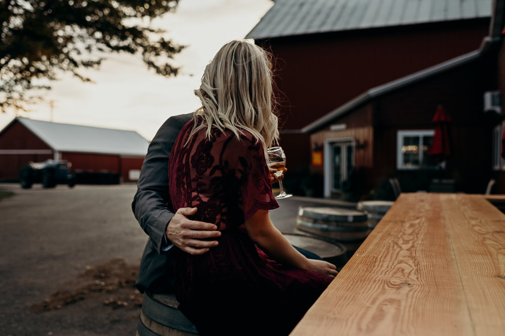 Engaged couple sits at an outdoor bar tasting wine at Apple Barn Orchard and Winery in Elkhorn, WI.