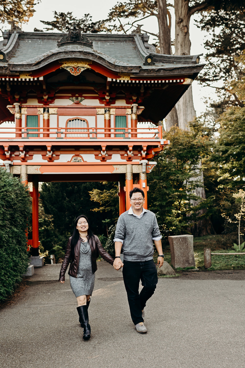 Engaged couple holding hands in front of the Thai pavillion at the Japanese Tea Garden in San Francisco's Golden Gate Park.
