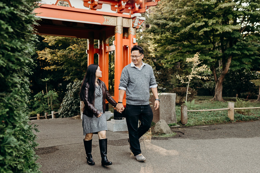Engaged couple holding hands and looking at each other in front of the Thai pavilion at the Japanese Tea Garden in San Francisco's Golden Gate Park.