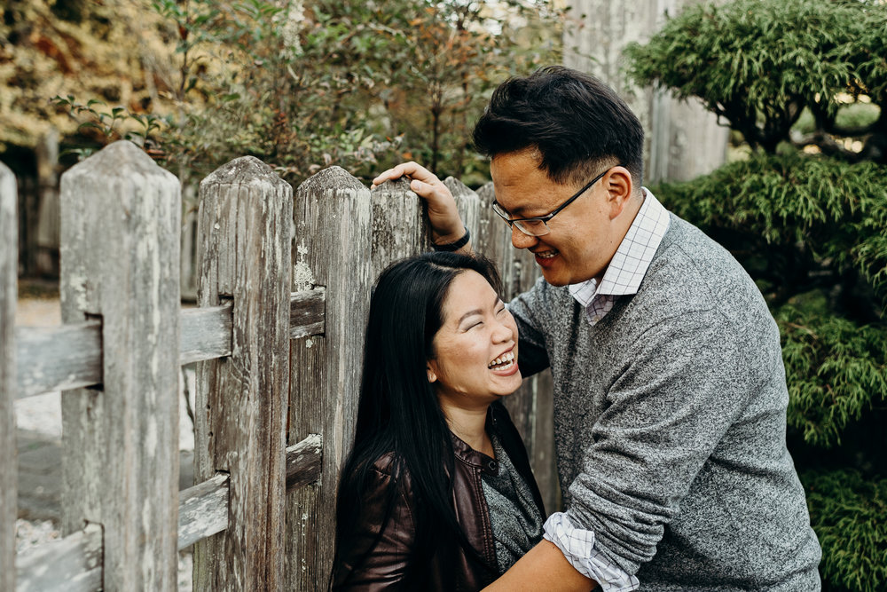 Woman leans back against a wooden fence and laughs as her fiance leans into her.