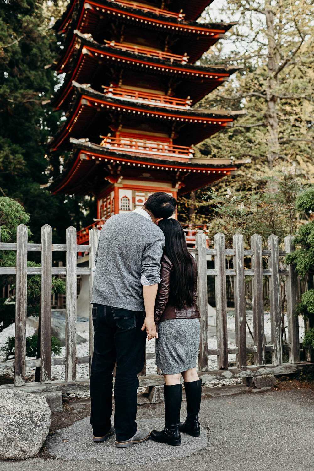 Engaged couple holds hands and looks at a red Thai pavilion.