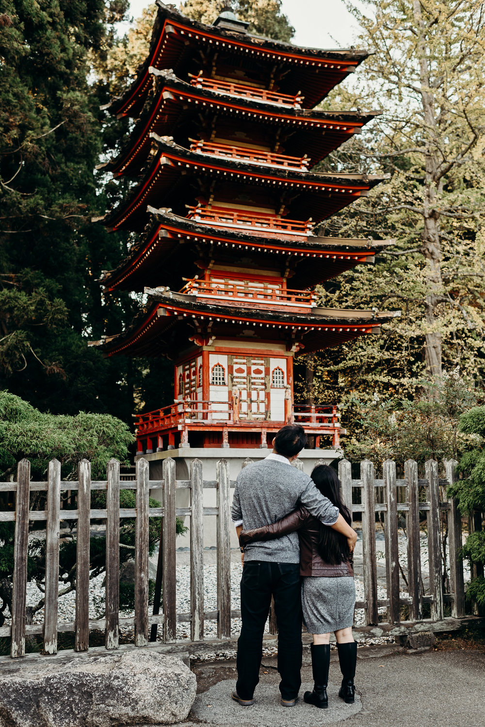 Engaged couple wraps their arms around each other's waists while looking at a red Thai pavilion.