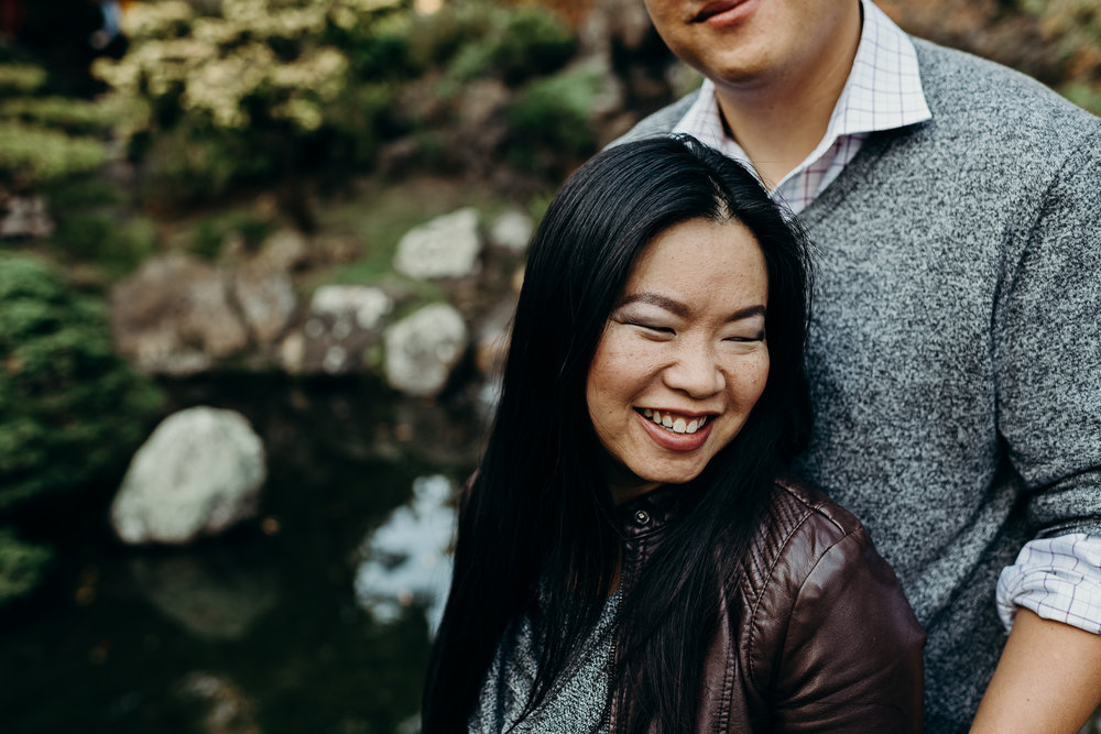 Woman smiles as she leans back into her fiance's chest.