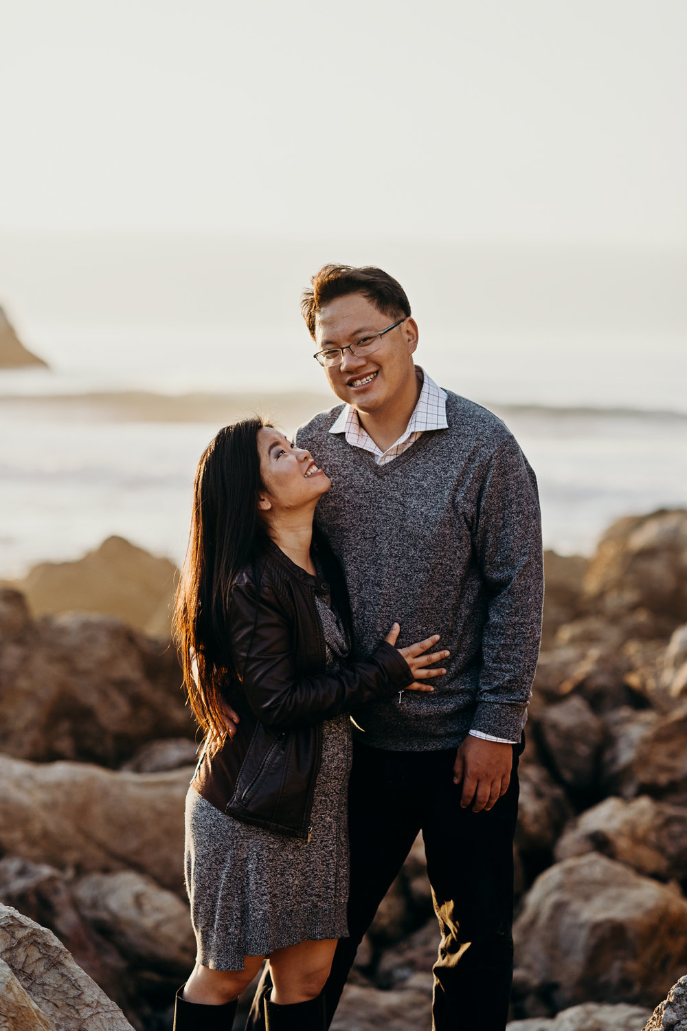 Man smiles at the camera as his fiance admires him.