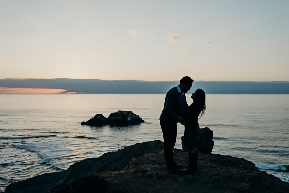 Silhouette of engaged couple holding each other during sunset at Sutro Baths in San Francisco, CA.