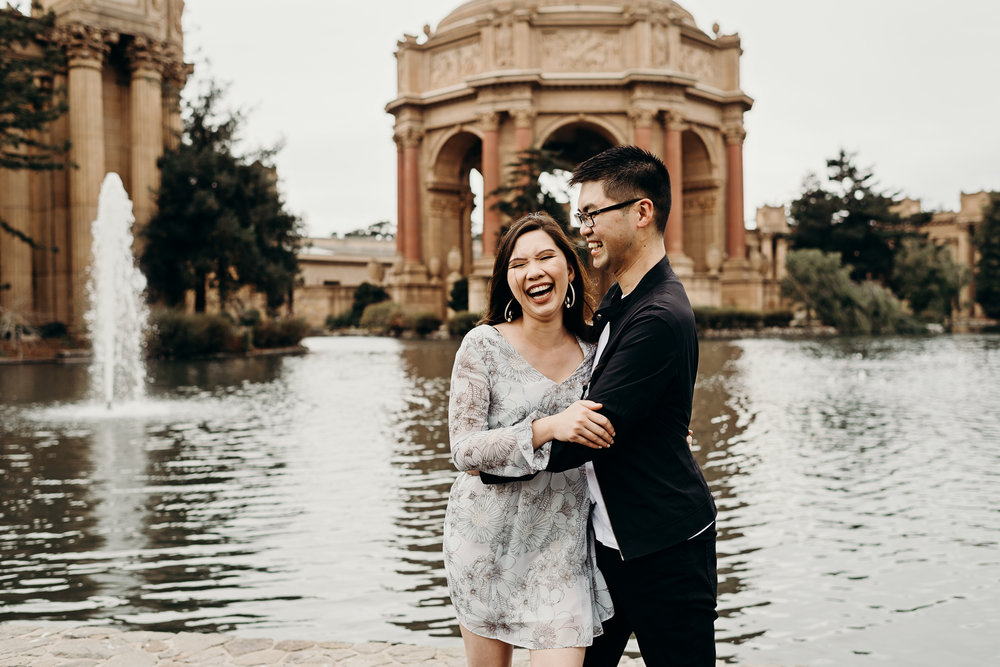 Engaged couple laughs at Palace of Fine Arts Theatre in San Francisco, CA.