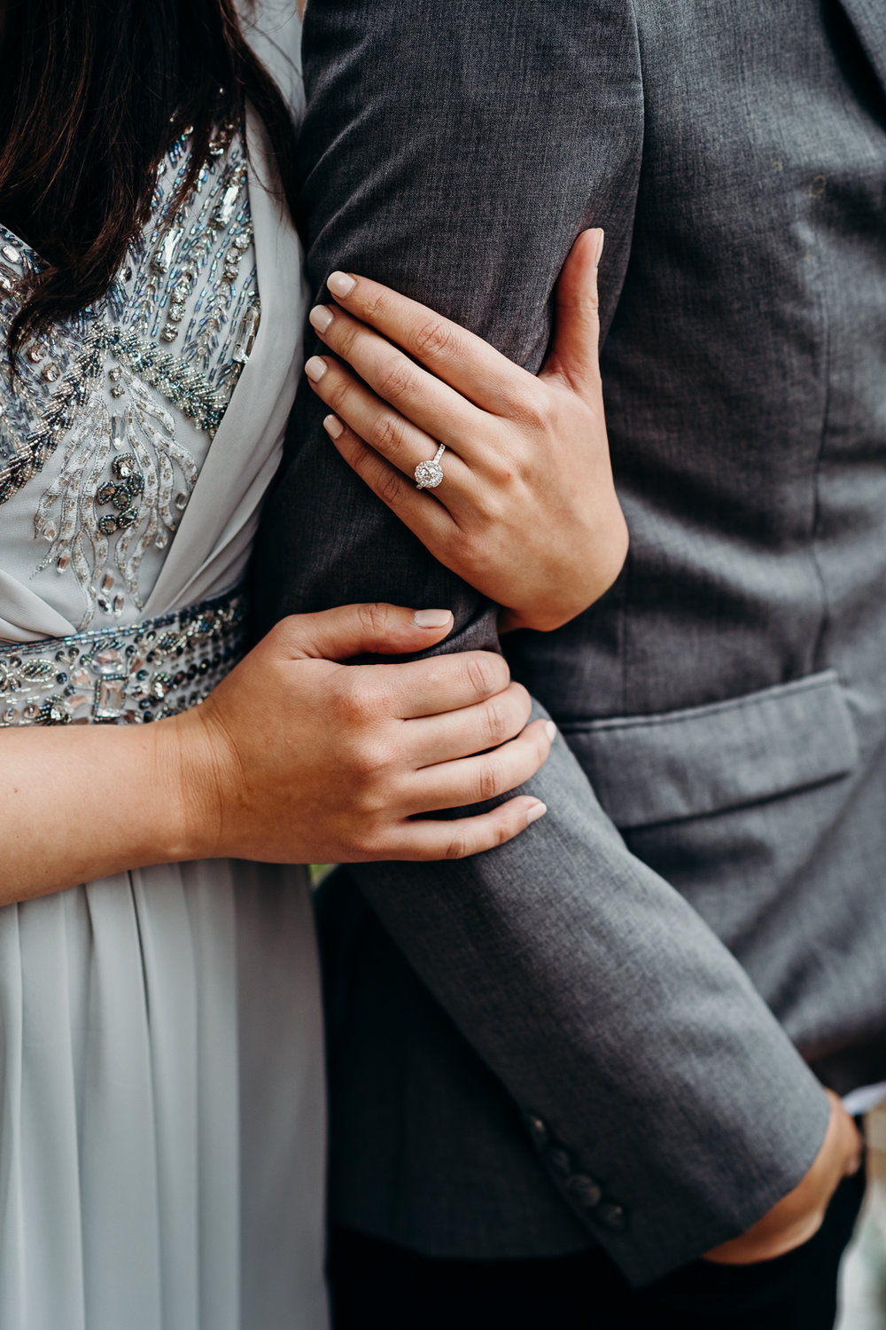 Woman shows her round cut engagement ring while holding her fiancé's arm.