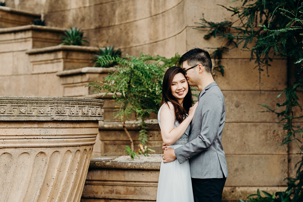 Man kisses his fiancé's forehead as she smiles at the camera.