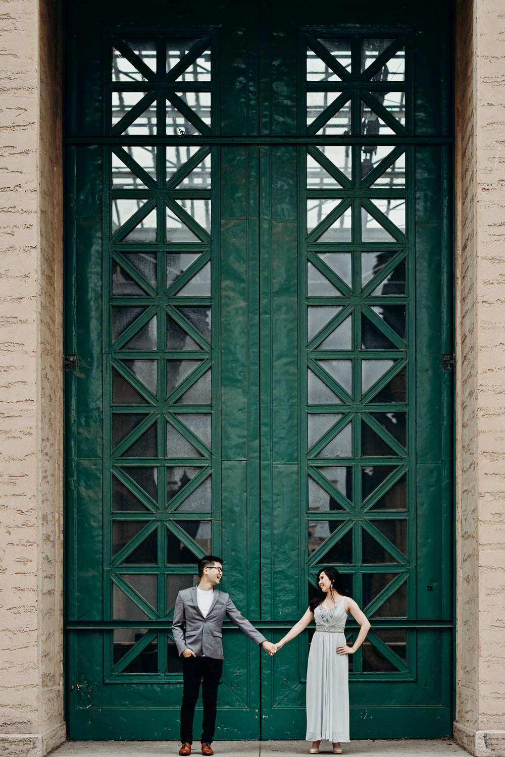 Engaged couple holds hands and looks at each other in front of a tall green door at Palace of Fine Arts.