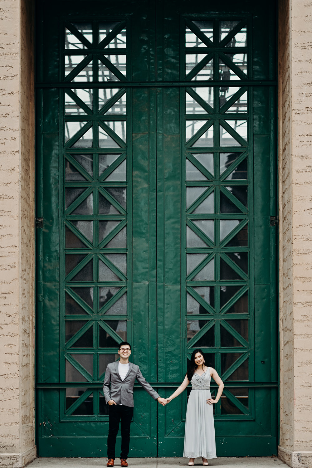 Engaged couple holds hands in front of a tall green door at Palace of Fine Arts Theatre in San Francisco, CA.