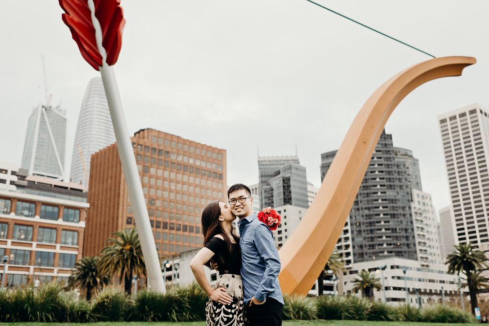 Woman kisses her fiancé's cheek in front of Cupid's Span with San Francisco in the background.